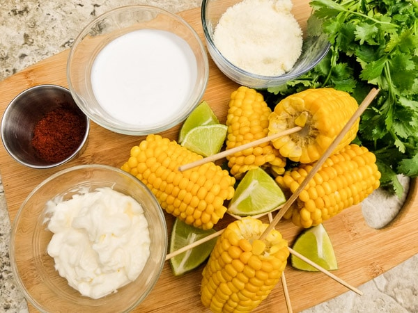 All ingredients displayed on wooden cutting board for Easy Delicious Mexican Street Corn (Elote)