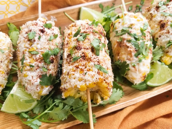Delicious Mexican Street Corn (Elote) with all the toppings. Made with sweet corn, mayonnaise, cotija cheese, ancho chili powder, lime and cilantro. Excellent appetizer or side dish! Served on a wooden platter.