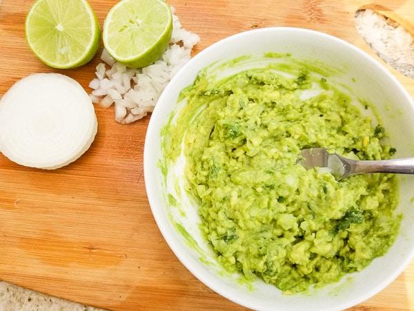 Guacamole ready for the Smoky Black Bean Avocado Tostadas in a white bowl.