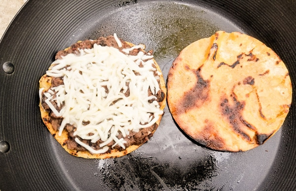 Warming tostadas with black bean puree and melting the shredded monterey jack cheese in a skillet to form the Smoky Black Bean Avocado Tostadas.
