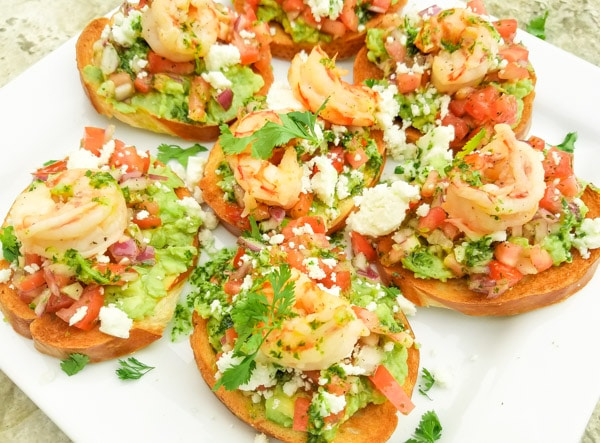 This Mexican Bruschetta Recipe is made with a fresh guacamole, tomatoes, jalapeños, garlic, cilantro, lime juice, topped with queso fresco and savory cooked shrimp.  (Shrimp optional)  Excellent snack or starter to any meal. Served on top of a white platter.