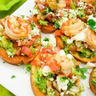 This Mexican Bruschetta Recipe is made with a fresh guacamole, tomatoes, red onions, jalapeños, garlic, cilantro, lime juice, topped with queso fresco and savory cooked shrimp.  (Shrimp optional)  Excellent snack or starter to any meal. Served on top of a white platter. | mexicanappetiersandmore.com