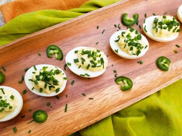 Jalapeno Deviled Eggs served on a wooden platter.