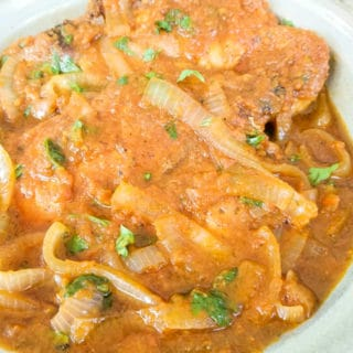 Chuletas de Puerco en Salsa (Pork Chops Braised in a Fresh Tomato Salsa) made in a simple tomato jalapeno based sauce with aromatic spices.  Tender pork chops that break apart with a fork and no need for a knife.  Serve pork chops on top of white or yellow rice.