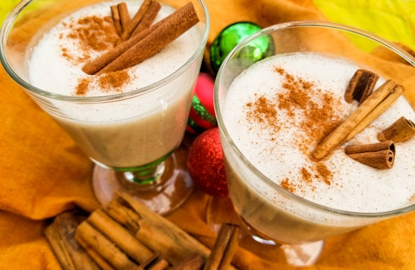 A delicious coquito recipe-coconut eggnog made with evaporated milk, coconut milk, cream of coconut, sweetened condensed, vanilla and cinnamon. Served with or without rum. Creamy and absolutely delicious! Served in small glass cups with cinnamon sticks.