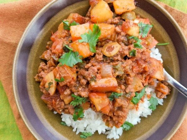 Authentic Mexican Picadillo recipe with potatoes on top of white rice served in a brown bowl.