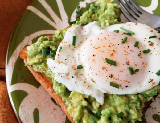 This simple poached egg and avocado toast is made with avocado spread that includes chives and cayenne pepper with a poached egg on toast and served on a green and white plate.