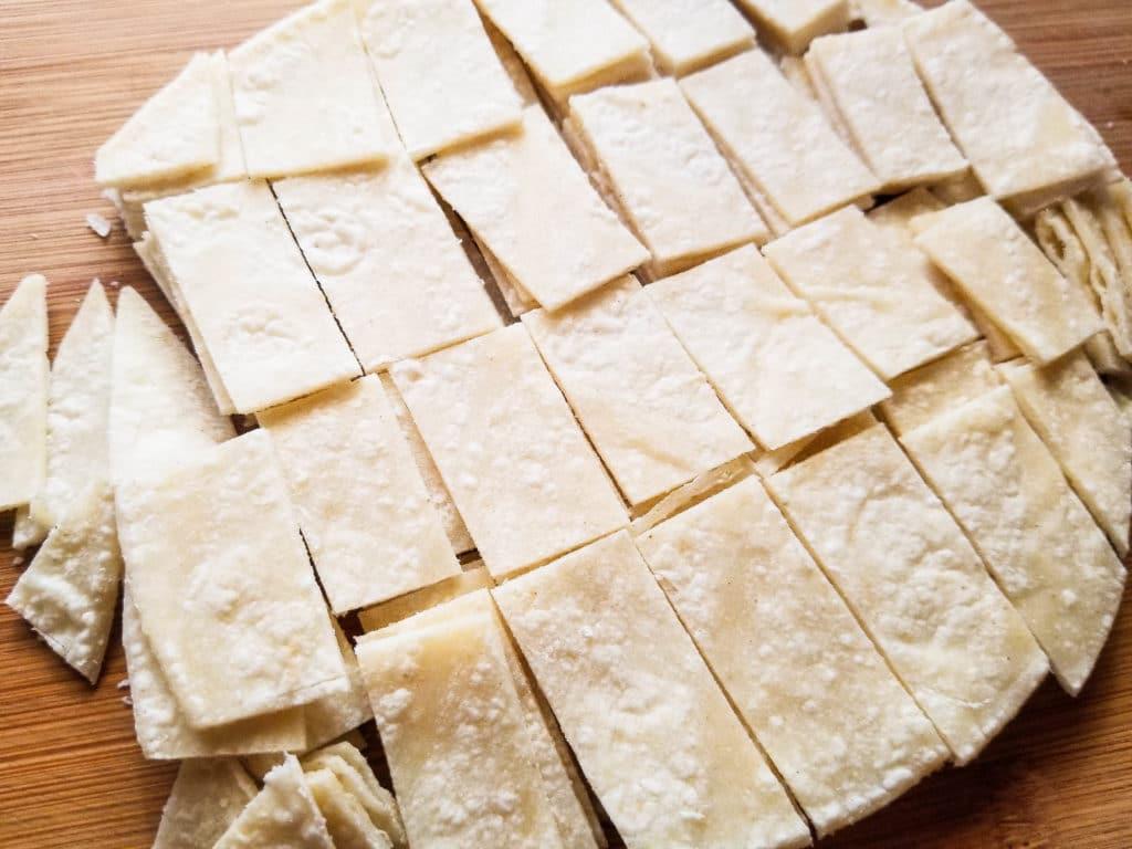 Corn tortillas cut into strips for Authentic Migas Recipe.