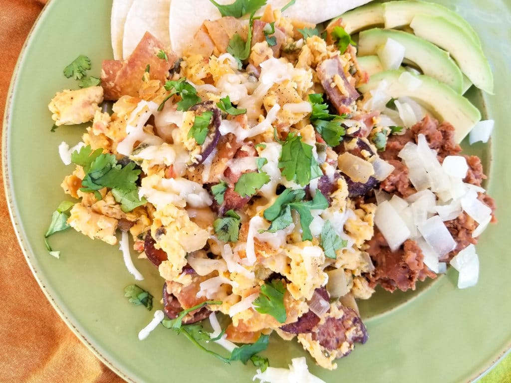 Authentic Migas Recipe with crispy corn tortilla strips, scrambled eggs with kielbasa sausage, onions, tomatoes, poblano pepper, jalapeno, garlic, cilantro, monterey jack cheese and refried beans, avocado slices on a green plate.