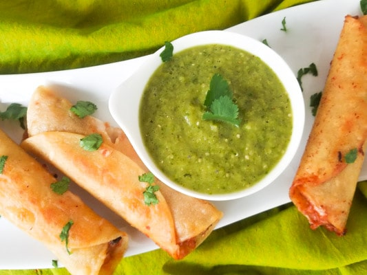 Chili Flautas served with salsa verde on a white platter.
