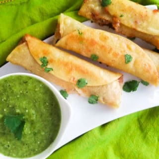 Chili Flautas with Salsa Verde served on a white platter.