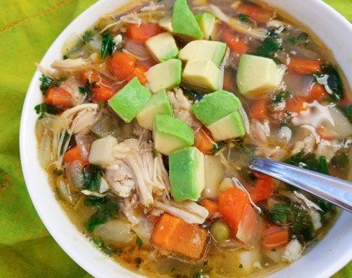 Low Carb Chicken Vegetable Soup made with mixed veggies, including peas, corn, green beans, carrots, onions, fresh chopped garlic and shredded chicken breast in a delicious chicken broth and topped with fresh cilantro and avocado cubes. Served in a white soup bowl.