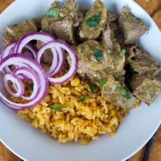 Slow Cooker Ribs with yellow rice and red onions on a white plate.