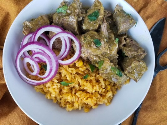 Slow Cooker Ribs served with yellow rice and red onions served in a white bowl.