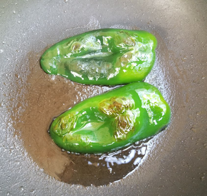 Poblano peppers cooking in a skillet for the Eggs In Poblano Pepper Boats