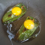 Eggs cooking inside the poblano peppers for the Eggs In Poblano Pepper Boats