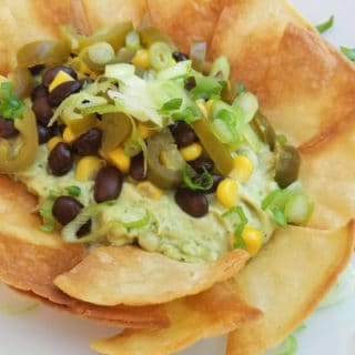 Vegan Avocado Dip with black beans, corn, scallions and homemade tortilla chips.