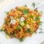 Arroz Mamposteao served on a white platter and topped with chopped scallions and cilantro.