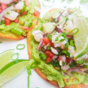 Shrimp Ceviche Tostadas on a white platter with lime wedges.