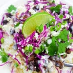 Morisqueta topped with red shredded cabbage, queso fresco, Mexican crema and served on a white plate.