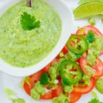 Avocado Lime Dressing in a small dressing bowl and tomato slices topped with avocado dressing with slivers of jalapeno and chopped scallions, served on a white platter.