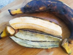 Ripe plantains (maduros) cut and sliced on a wooden cutting board for the pastelón.
