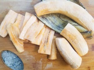 Ripe plantains cut and sliced on a wooden cutting board for the pastelón.