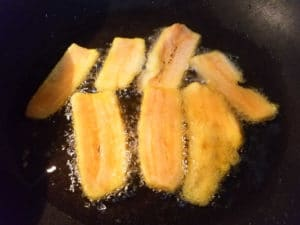 Plantains frying in a skillet for the pastelón.