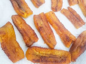 Cooked ripe plantains draining on paper towels for the pastelón.