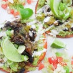 Avocado and Chipotle Mushroom Tostadas served on a white platter and topped with lime wedges.