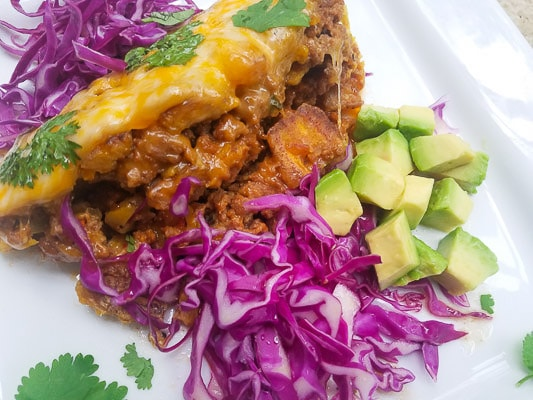 Pastelón served on a white platter with avocado cubes and shredded red cabbage.