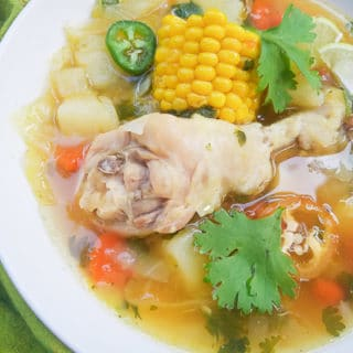 Caldo de Pollo (Mexican Chicken Soup) with carrots, onion, green cabbage, corn cob pieces and jalapenos served in a white bowl.