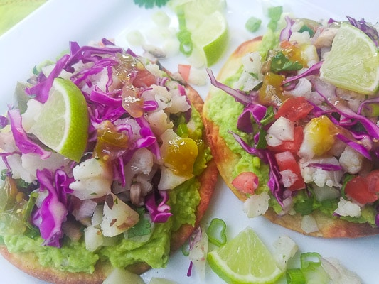 Cauliflower Ceviche Tostadas with guacamole. shredded red cabbage and salsa verde served on a white platter.