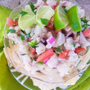 Cauliflower Ceviche served in a glass bowl with tortilla chips and lime wedges.