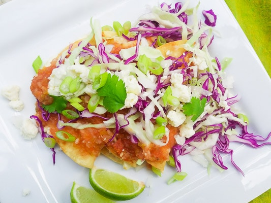 Entomatadas stuffed with queso fresco, topped with a savory tomato sauce, shredded red cabbage, sliced white onions and scallions. These entomatadas are served on a white plate with lime wedges.