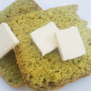 Slices of Avocado Bread topped with butter.