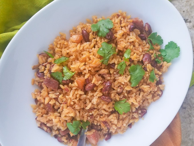 Puerto Rican Rice and Beans (Arroz y Habichuelas) served in a large white platter and topped with fresh chopped cilantro.