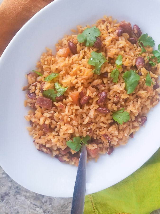Puerto Rican Rice and Beans (Arroz y Habichuelas) served in a large white platter and topped with freshed copped cilantro.