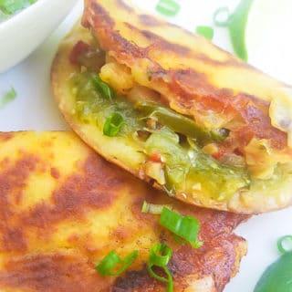 Tacos Gobernador served with salsa verde on a white platter.