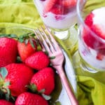 Fresas con crema (Strawberries and Cream) served in small transparent glasses with a side of fresh strawberries served on a transparent plate with a fork on top of a green lime napkin.