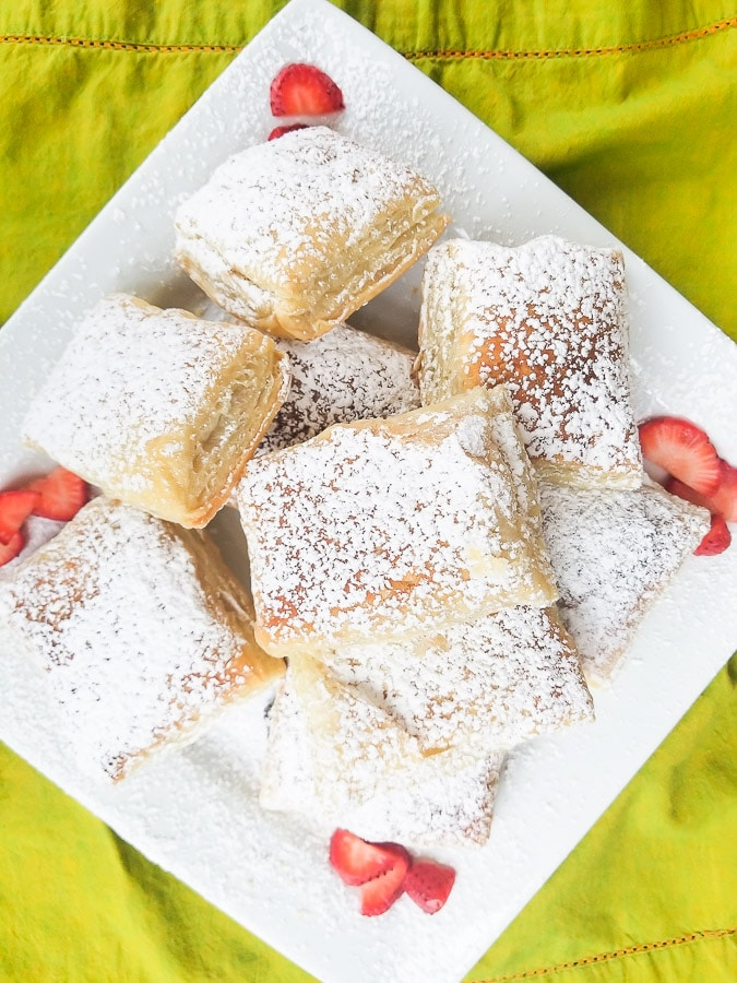 Pastelillos de Guayaba served on a beautiful white platter surrounded by strawberry slices.