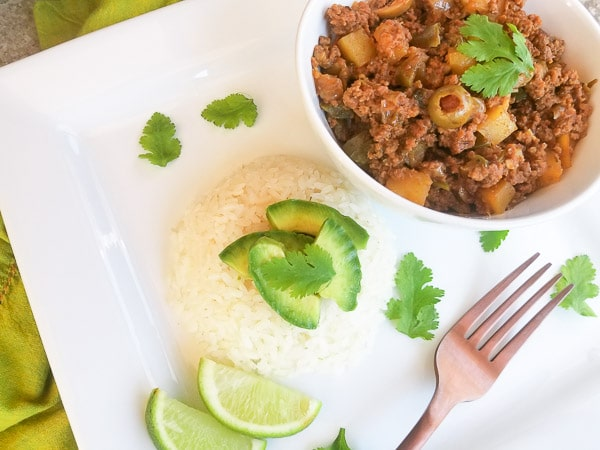 Carne Molida served on a white platter with white rice and avocado.