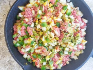 Raw ground meat with onions, peppers, sofrito, garlic and spices in a cast iron skillet ready to cook for the canoas de platano.