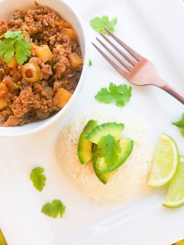 Carne Molida (Puerto Rican Picadillo) served on a white platter with white rice and avocado.