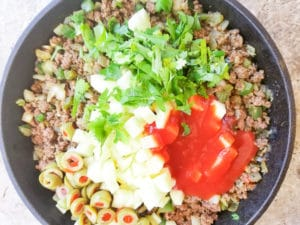 Almost fully cooked Carne Molida (Puerto Rican Picadillo) topped with the potatoes, cilantro, tomato sauce and olives in a cast iron skillet.