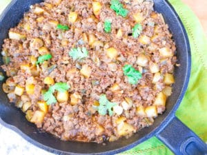 Fully cooked Carne Molida (Puerto Rican Picadillo) topped with the potatoes, cilantro, tomato sauce and olives in a cast iron skillet.