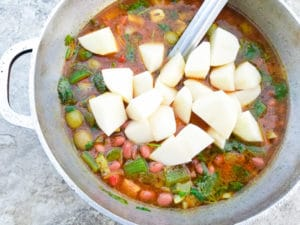 All the ingredients for Habichuelas Guisadas (Puerto Rican Beans) cooking in a caldero (pot).