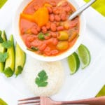 Habichuelas Guisadas (Puerto Rican Beans) on a white plate served with avocado slices and lime wedges.