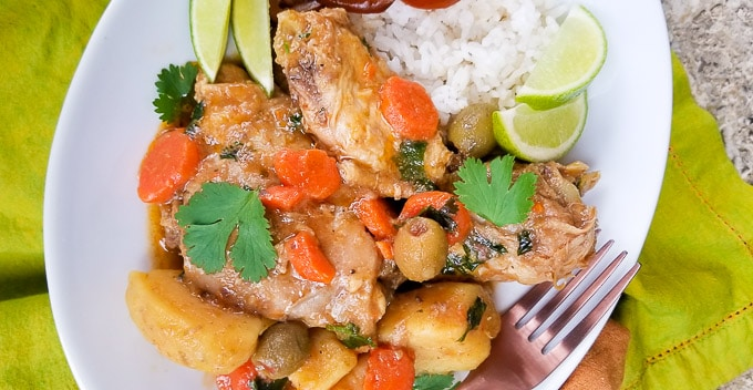 Pollo Guisado (Puerto Rican Chicken Stew) with carrots, potatoes, olives, cilantro, spices in a delicious savory chicken broth served with white rice in a large white deep dish.