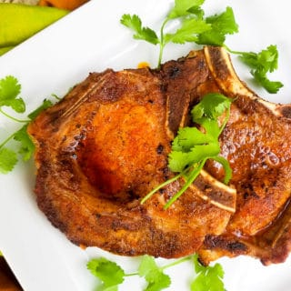 Baked pork chops served on a large white platter and topped with cilantro sprigs.